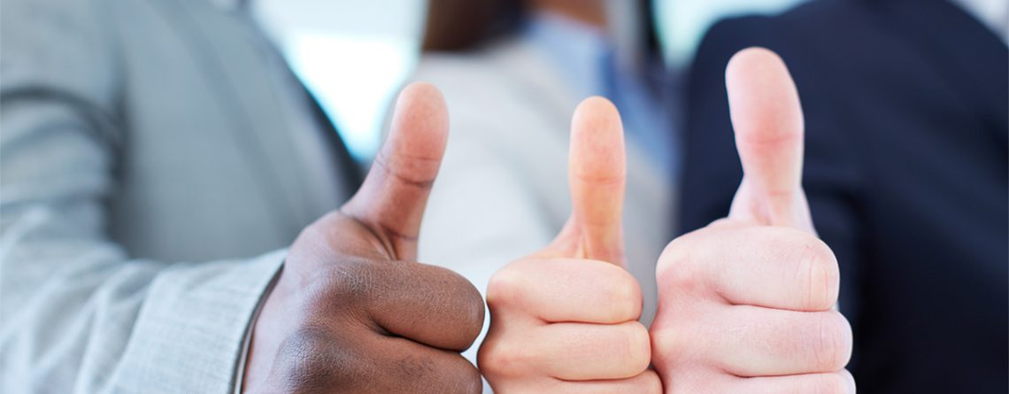 close up of the hands of three people with thumbs up