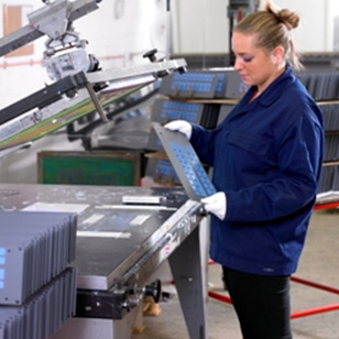 a woman operating a screen printing machine