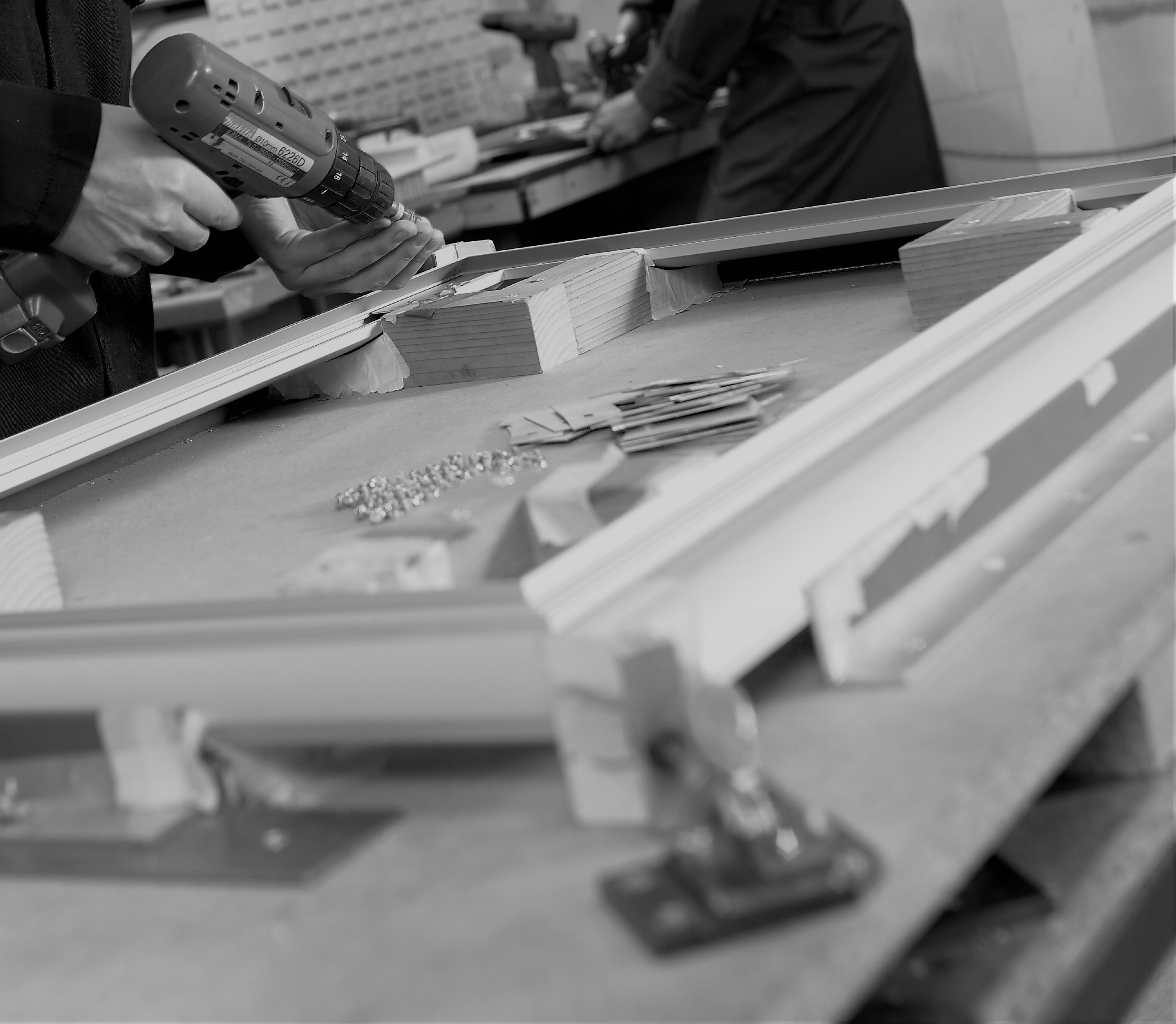 black and white image of a mans hands carrying out the assembly process