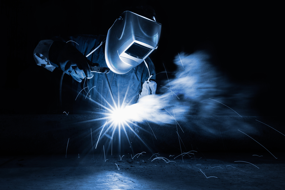 welder with sparks surrounding them